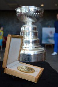 toimitusjohtaja Astrid Venäläinen ja LA Kingsin kykyjenetsijä Christian Ruuttu yhdessä Nobelin rauhanpalkinnon ja Stanley Cupin kanssa.
